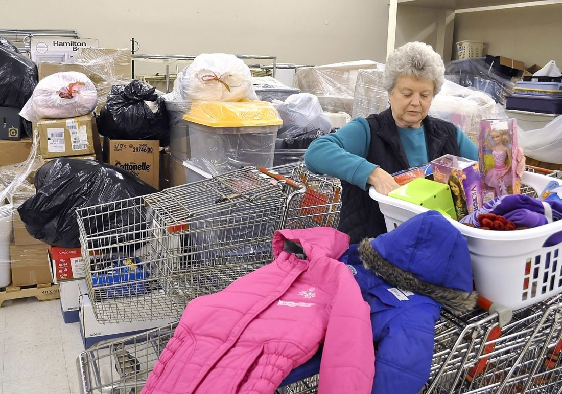 -Messenger file photo by Joe Sutter  Gwen Anderson, Operation Christmas co-chair, unpacks new children's coats and toys she bought on sale during the 2012 operation at its former location in the Crossroads Mall.  Behind her, piles of new donated items wait to be sorted for the group's big Christmas giveaway. This year donations will be accepted beginning Nov. 14 at the Trolley Center, 900 Central Ave.