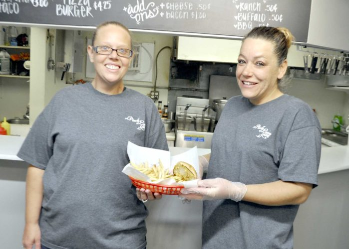 -Messenger photo by Peter Kaspari  A Pinch of Love Cafe owners Angie Reiter, left, and Crystal Mikesell-Lowrey, pose with one of their daily specials, a chili cheesburger, recently. The two recently opened the cafe, which is entire family-run.