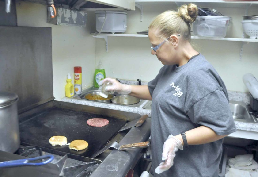 -Messenger photo by Peter Kaspari  Angie Reiter, co-owner of A Pinch of Love Cafe, seasons a hamburger for the daily special chili cheeseburger.