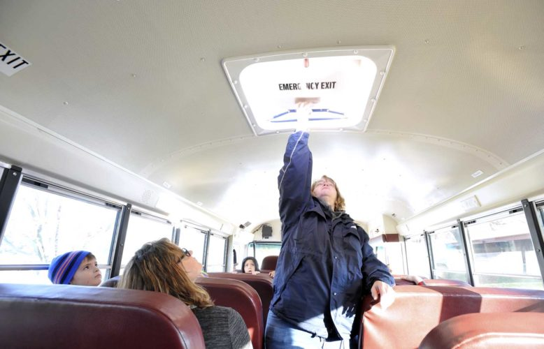 -Messenger photo by Hans Madsen  Michelle Ely, a Fort Dodge Community School District bus driver, demonstrates how the roof hatch on a school bus works Wednesday morning during a school bus evacuation drill at Cooper Elementary.