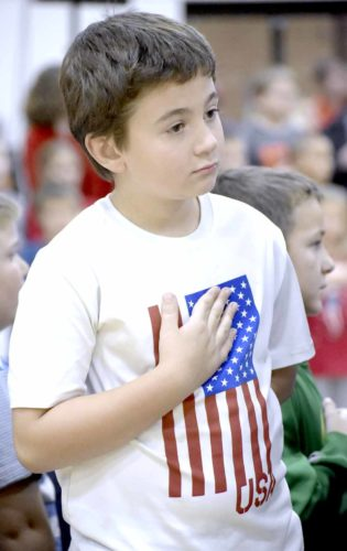 -Messenger photo by Chad Thompson  Cameron Wood, 8, a third grader at Manson Northwest Webster Elementary School, places his hand on his heart during the school's Veterans Day program Friday afternoon in the elementary gym.