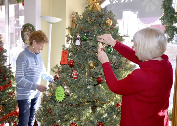 -Messenger photo by Peter Kaspari  Volunteers Marti Doyle, left, and Joan Tibbitts decorate a Christmas tree at The Key on Central. The two women are among several volunteers who decorate the store for Christmas every year. The Christmas items are also for sale.