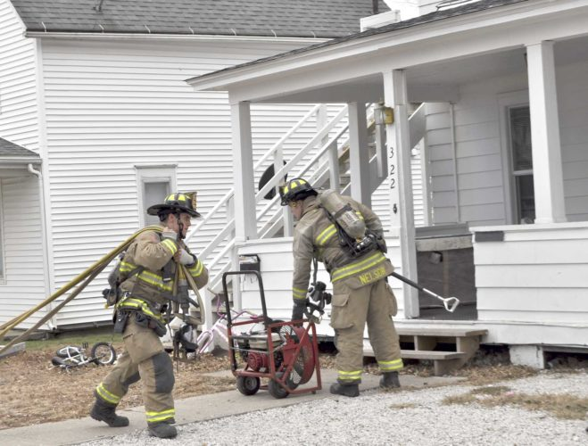 -Messenger photo by Bill Shea   Fort Dodge firefighter Zach Rickman stretches a hoseline while firefighter Greg Nelson sets up a ventilation fan Friday afternoon at 322 N. Eighth St. The fire was confined to a back inside wall of the building, and no one was hurt.