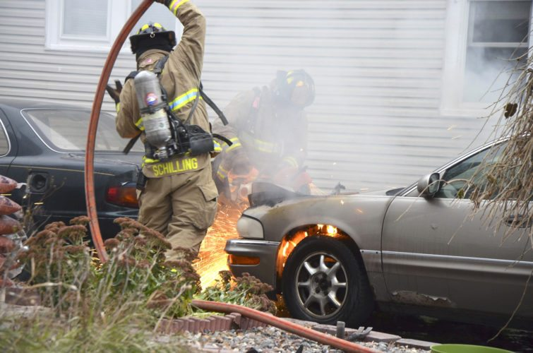 -Messenger photo by Peter Kaspari   Fort Dodge firefighter Randy Schilling, left, prepares to use the hose as firefighter Andy Hull uses a saw to cut open the hood of a burning car Monday afternoon at 1436 Fourth Ave. N. Firefighter Chuck DeBaun said the car's owner went to start it after it had been idle for about four days. When she tried to start it, she heard a pop and the car caught fire. DeBaun said the fire was extinguished quickly, but the car is a total loss. He said the fire was contained to the car and did not spread to a second car or the home. The Fort Dodge Police Department also responded to the scene.