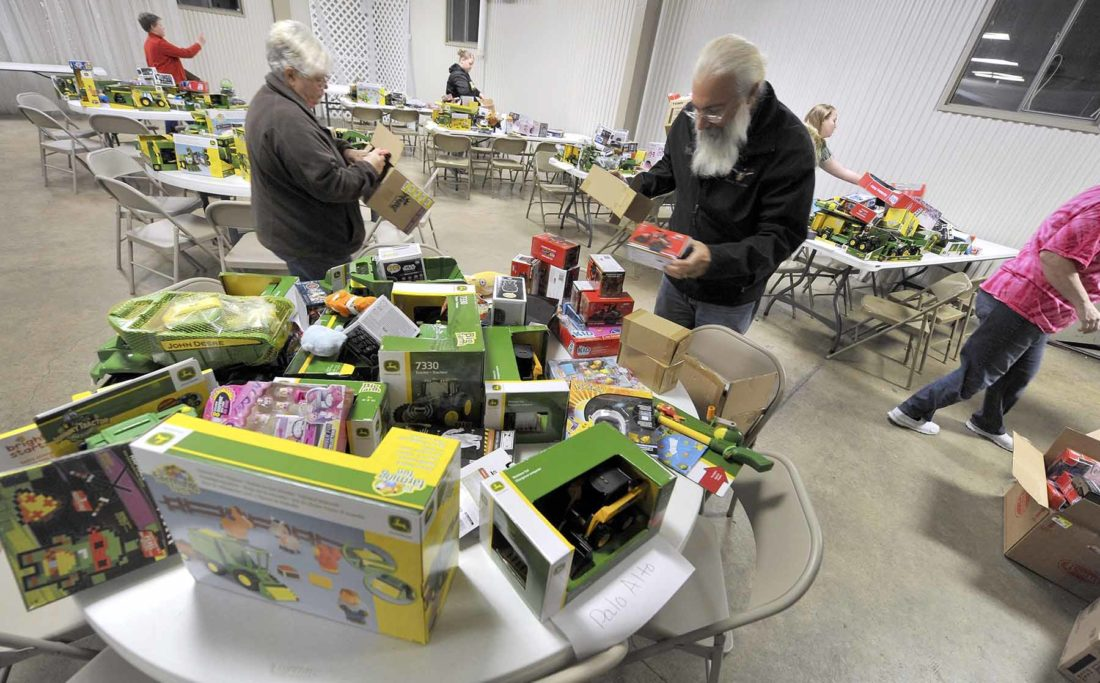 """-Messenger photo by Hans Madsen  Mark Loots, state trustee for A Brotherhood Aimed Toward Education helps open packages of new toys Thursday night at Rides Event Center in Fort Dodge. According to ABATE District 10 cordinator Melissa Morey, many of the toys were collected during the district's Toy Run and Auction held on Sept. 16. """"They brought an new unwrapped toy to participate,"""" she said. Toys were also collected at drop off sites and and several local bars. Toys were also purchased with donations made at the run and other events. """"We bought 953 toys just from WalMart,"""" she said. Toys were also donated by several local businesses including West Bend Red Power that contributed a number of Interantional Harvestor equipment toys. The toys will be distributed to children in need in the 11 counties that make up District 10 by local agencies."""