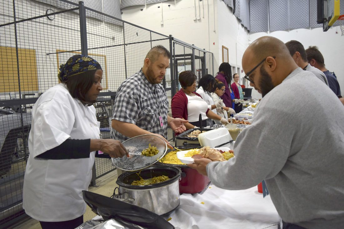-Messenger photo by Joe Sutter  Michelle Taylor, left, and Jacob Alvarez serve Jaymes Stark at the front of a line of men at the Fort Dodge Correctional Facility for the annual Thanksgiving dinner put on by Agape Kingdom Dominion Ministries. The volunteers said these men are like family, since they are all part of the family of God.