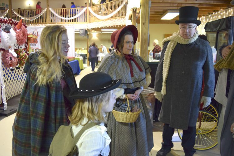 -Messenger photo by Joe Sutter  The Cratchetts from 'A Christmas Carol' and other Dickens characters welcome visitors to the vendor displays at the Fort Museum and Frontier Village's Dickens Christmas Saturday. Bob Cratchett at right, played by Steve Farr; Mrs. Cratchett (Jodi Delaney); one of the Cratchett kids (Bailey Schuster); and Nancy from 'Oliver Twist' (Jessica Einwalter). Santa Claus was also in attendance for the first of what will become an annual event, said Misty Mackay. Although the Fort Museum mostly portrays the frontier era, not Dickens' Victorian era, the museum's history spans 100 years, meaning it sort of fits.