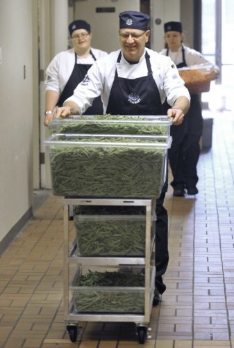 -Messenger photo by Hans Madsen  Iowa Central Community College Culinary Arts Program student Rodney Walters, of Rockwell City, pushes a cart holding some of the 216 pounds of green beans that will be served at the annual Community Thanksgiving Dinner at Fort Dodge Ford.