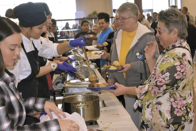 -Messenger photo by Chad Thompson  Iowa Central Community College culinary arts students serve a line of guests during the annual Thanksgiving dinner at Fort Dodge Ford Lincoln Toyota Thursday afternoon.