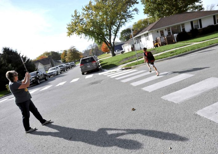 -Messenger photo by Hans Madsen  Mary Rethwisch, Cooper Elementary School staff crossing guard, holds up traffic as the first student to leave school recently makes a beeline for the sidewalk leading home. Potential changes would affect where some students will attend classes.