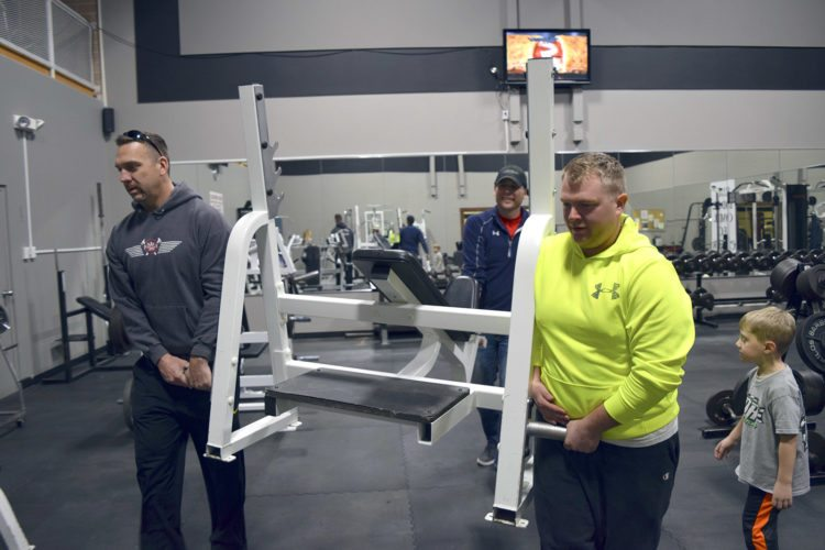 -Messenger photo by Joe Sutter  Fort Dodge Firefighters Jason reynolds, left, and Mike Wiltzius with REC Associate Director Matt Hanson remove one of the old weight benches at the rec center recently. The REC donated some old equipment to the fire department to make new for new items.