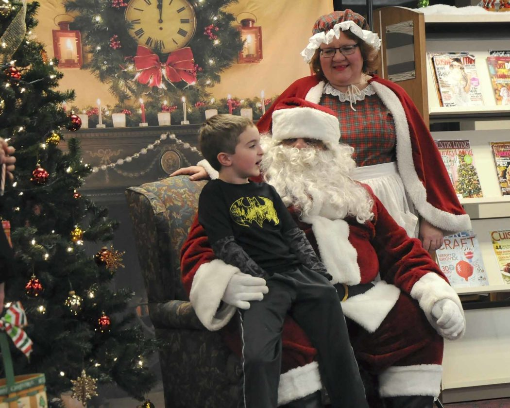 -Messenger photo by Joe Sutter  Grayson Chance, 7, tells Santa about his Christmas wishes. The line reached out the front doors at the library with children waiting to see Santa Claus at the Lights on Central celebration in 2016.
