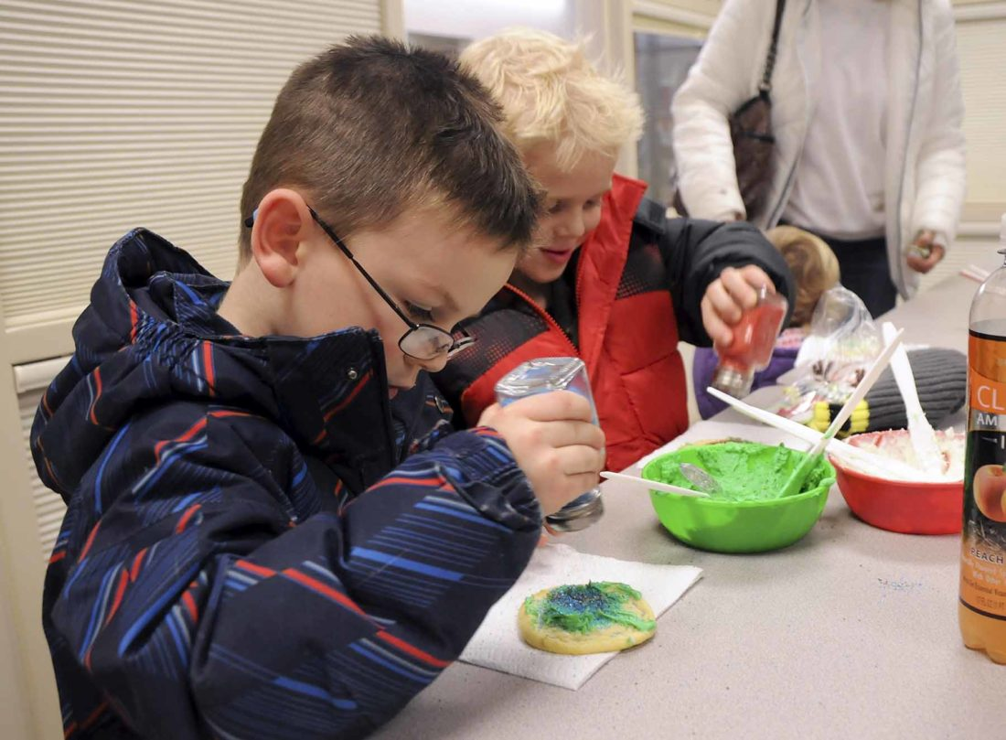 -Messenger photo by Joe Sutter   Ronan Kavanaugh, 4, left, and James Kavanaugh, 5, add sprinkles to their Christmas cookies after applying frosting at Lights on Central in 2016. The cookie station proved to be a popular stop.  Ronan Kavanaugh, 4, left, and James Kavanaugh, 5, add sprinkles to their Christmas cookies after adding some frosting at Lights on Central Monday. The cookie station proved to be a popular stop.