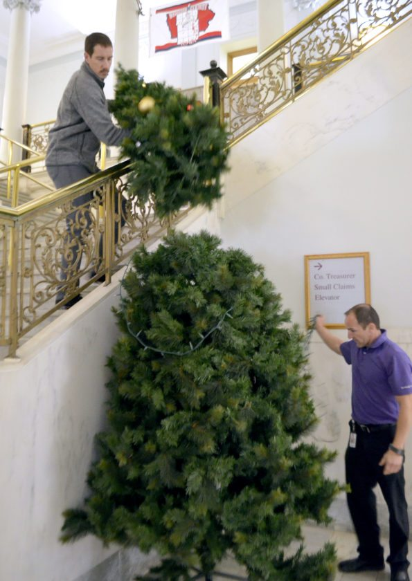 -Messenger photo by Joe Sutter  Webster County Supervisor Nick Carlson, left, and Assistant County Engineer Jamie Johll piece together the second of two large Christmas trees which stand on each side of the stairs at the courthouse.