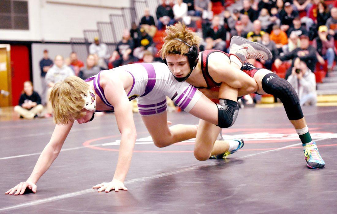 -Messenger photo by Britt Kudla Drew Bennett of Fort Dodge wrestles against Johnston's James Edwards on Thursday