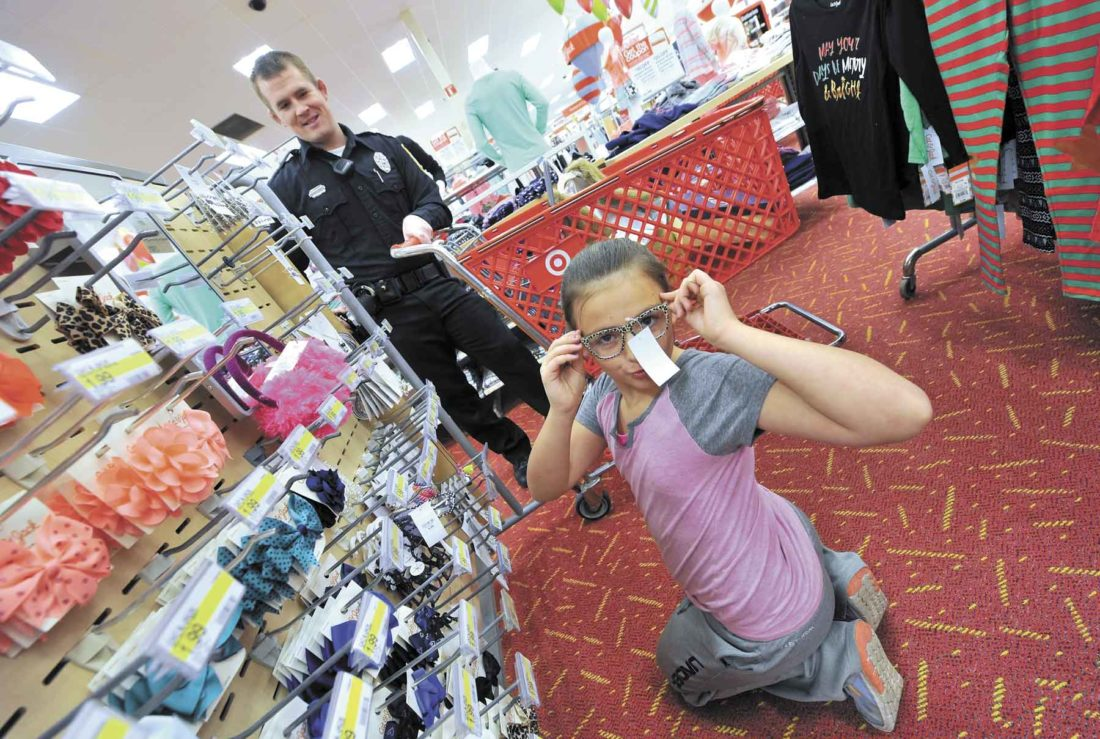 -Messenger file photo by Hans Madsen Fort Dodge Police Officer Matt Burns watches as Cassie Welch, 10, of Fort Dodge, tries on a pair of stylish glasses at the Fort Dodge Target Store during the annual Santa Cops event in 2016. The young aspiring fashion consultant had purchased many other items for her family.