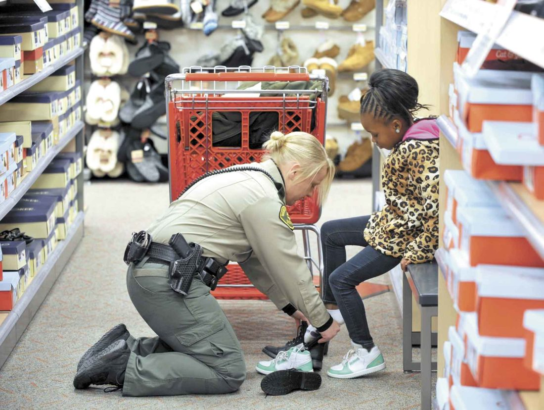 -Messenger file photo by Hans Madsen Webster County Sheriff's Deputy Amy Stringer gives Diamond Altman, 8, of Fort Dodge, a helping hand as she tries on a new pair of boots at the Fort Dodge Target Store during the annual Santa Cops event in 2016.