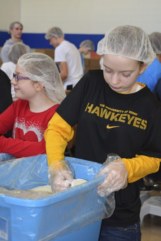 -Messenger photo by Peter Kaspari  Grace Casciato, 12, right, and her sister, Abigail Casciato, 10, both of Fort Dodge, work the assembly line packing bags of food for starving children.