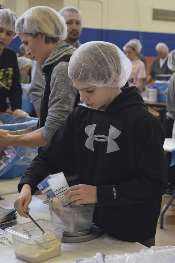 -Messenger photo by Peter Kaspari  Ayden Johanson, 12, of Fort Dodge, makes sure there's enough rice in a package that will be sent to a starving child somewhere in the world. Johanson was participating in the Feed My Starving Children MobilePack event Saturday.