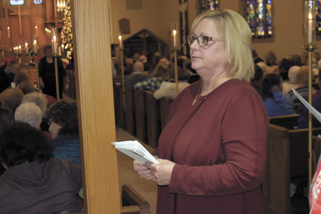 -Messenger photo by Chad Thompson  Keely Gunderson, of Fort Dodge, holds a stack of A Time for Angels programs during the annual service at St. Olaf Lutheran Church Sunday afternoon. Gunderson started the remembrance service almost 20 years ago.