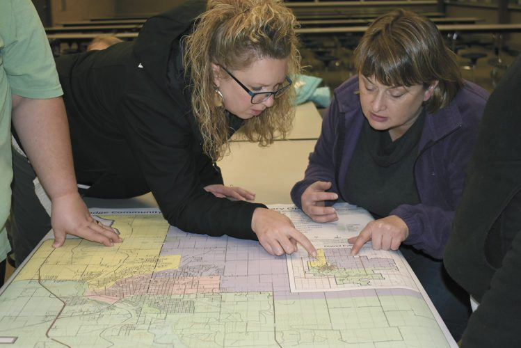 -Messenger photo by Chad Thompson  Lori Evans, left, and Lynette Nielson, both of Fort Dodge, look over some potential changes to Fort Dodge Community School District elementary boundaries during a public forum Monday night at the Fort Dodge Middle School.