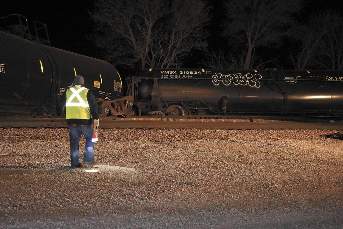 -Messenger photo by Chad Thompson  A Canadian National Railway employee walks with a lantern near a train derailment at Hayes Avenue and 201st Street near Barnum Thursday night.