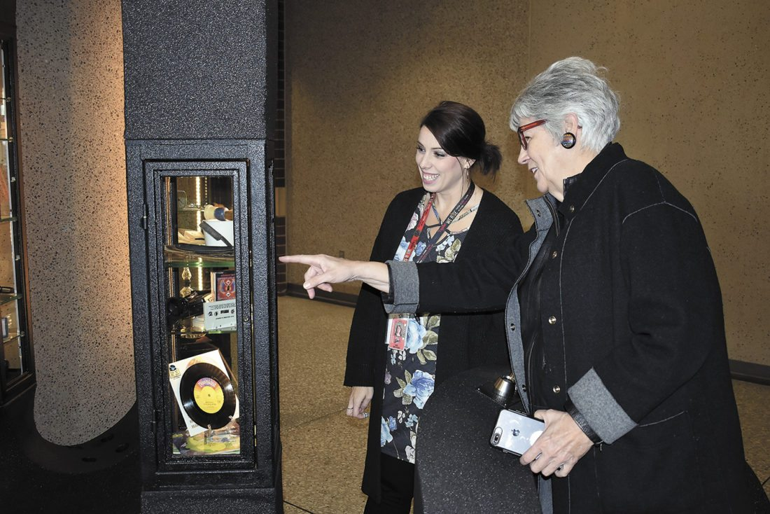 -Messenger photo by Chad Thompson  Judy Perkins, a member of the Catherine Vincent Deardorf Charitable Foundation, front, and Amanda Becker, a coordinator for the Cabinet of Obsolescence, look over the cabinet at the Fort Dodge Middle School Tuesday morning.