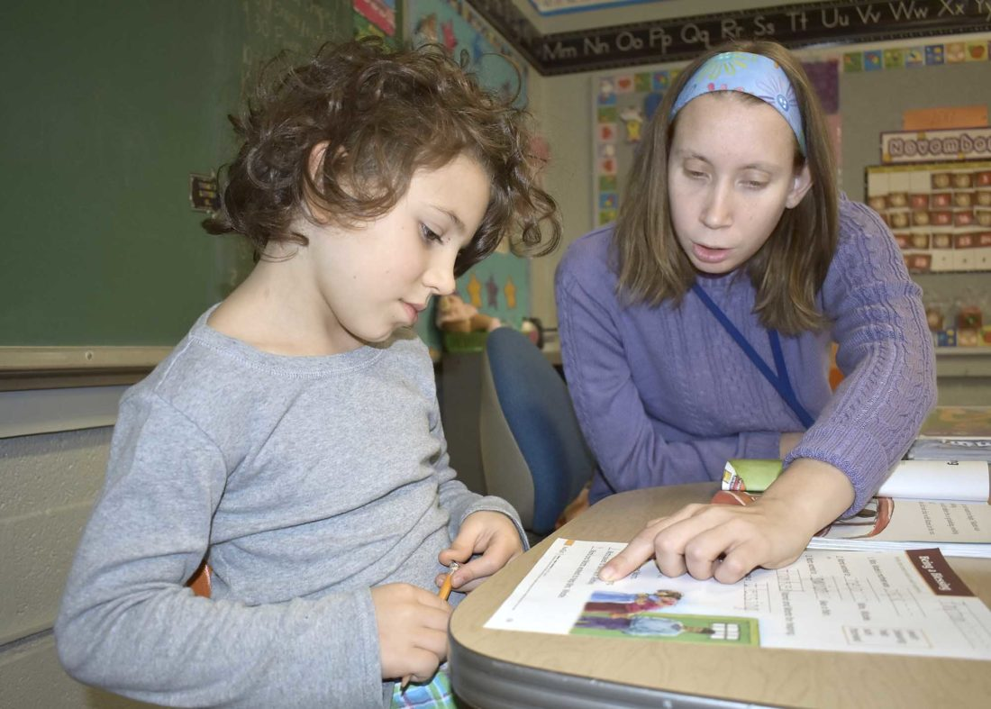 -Messenger photo by Chad Thompson  Payton Boone, 7, of Fort Dodge, front, gets some help from Carrie Alberston, first grade teacher at Community Christian School, recently.