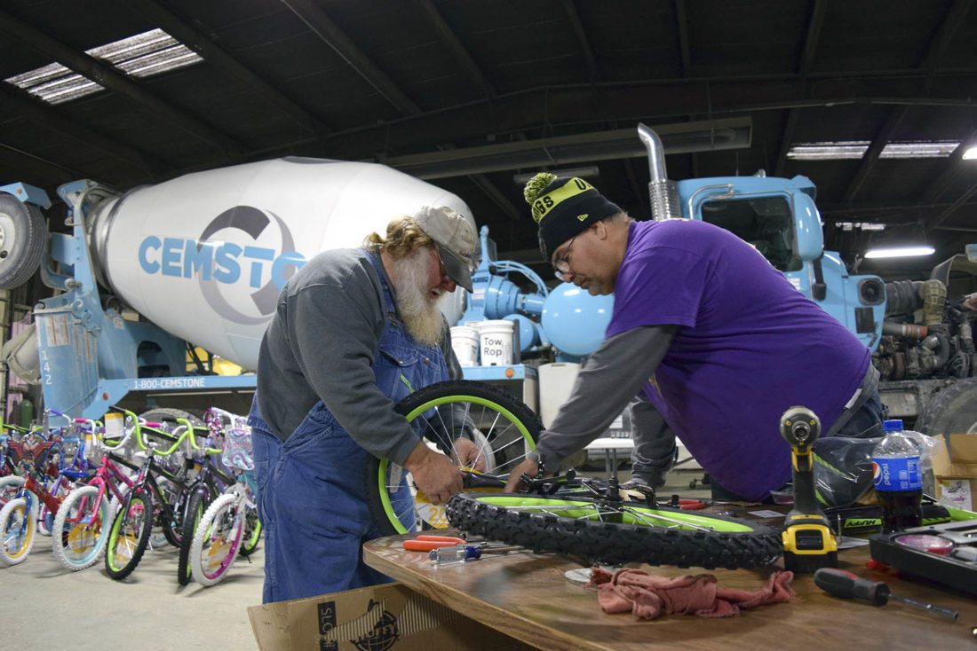 -Messenger photo by Joe Sutter  Rocky Davis, left, and Randy Buenting put together a bike during the Bikes for Tykes project Saturday morning at Cemstone Concrete. Buenting said the company has been taking part in the program for seven years now, and donated 67 bikes this year.