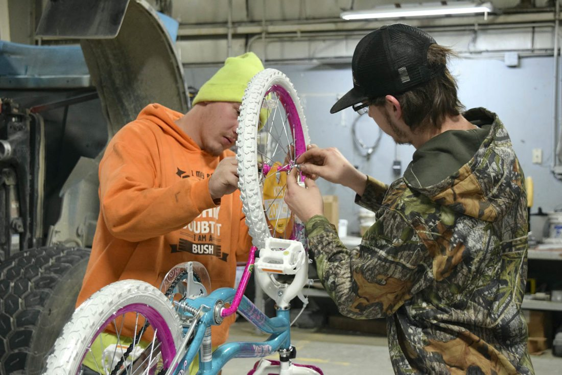 """-Messenger photo by Joe SutterMany """"elves"""" make light work. Cole Bush, left, and Verlyn Richardson make it sort of a competition to see how quickly they can assemble bicycles, while helping out family at Cemstone Concrete's Bikes for Tykes assembly day Saturday morning."""