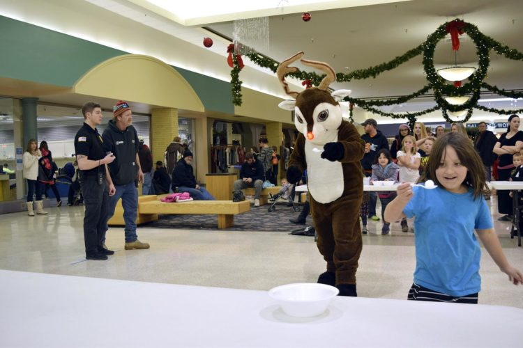 "-Messenger photo by Joe Sutter  Zionah Clark, 6, of Fort Dodge, races with Rudolph during the second annual Reindeer Games at the Crossroads Mall Saturday afternoon, while all of the other ""reindeer"" wait their turn. The event offered photo opportunities, candy and games, and family fun at the mall. Reindeer Games is one of several events the mall has planned for the holiday season.  On Dec. 16, it will host a holiday showcase featuring vendors, live entertainment, activities and gift-wrapping, as well as festivities throughout the mall.  On Dec. 22, the mall will be hosting Ugly Christmas Sweater Day. Visitors are encouraged to wear ugly sweaters, and mall employees will be wearing theirs as well."