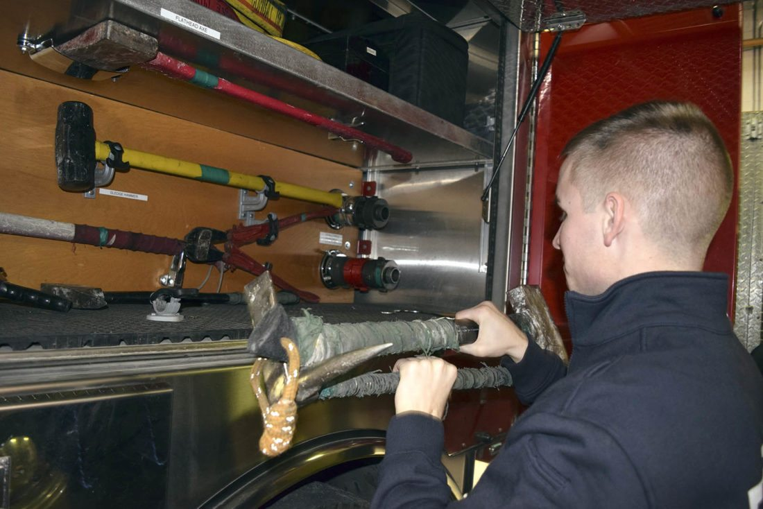 -Messenger photo by Peter Kaspari  Fort Dodge Firefighter Devon Schuster removes a Halligan tool and a flat-head axe from a fire engine recently. Schuster has been with the Fire Department for a year and three months.