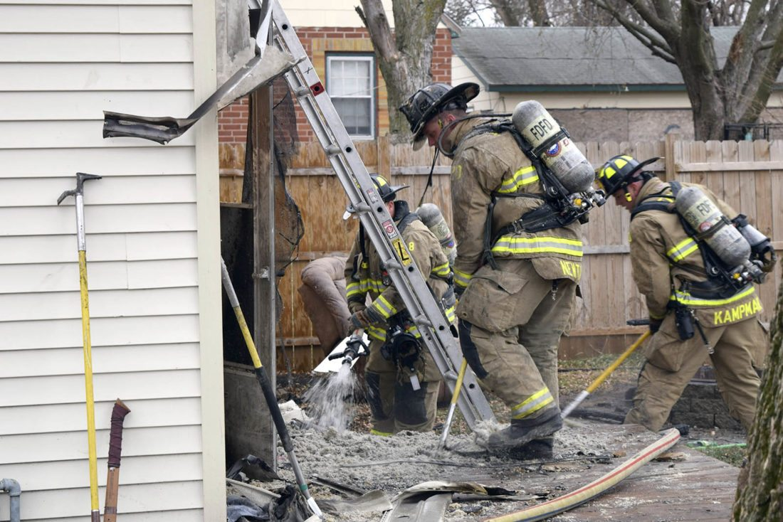 -Messenger photo by Bill Shea   Fort Dodge firefighters hose down insulation and other debris following a house fire Monday afternoon at 3107 Eighth Ave. S. The fire, which started outside the house, charred the back wall and spread into the attic.