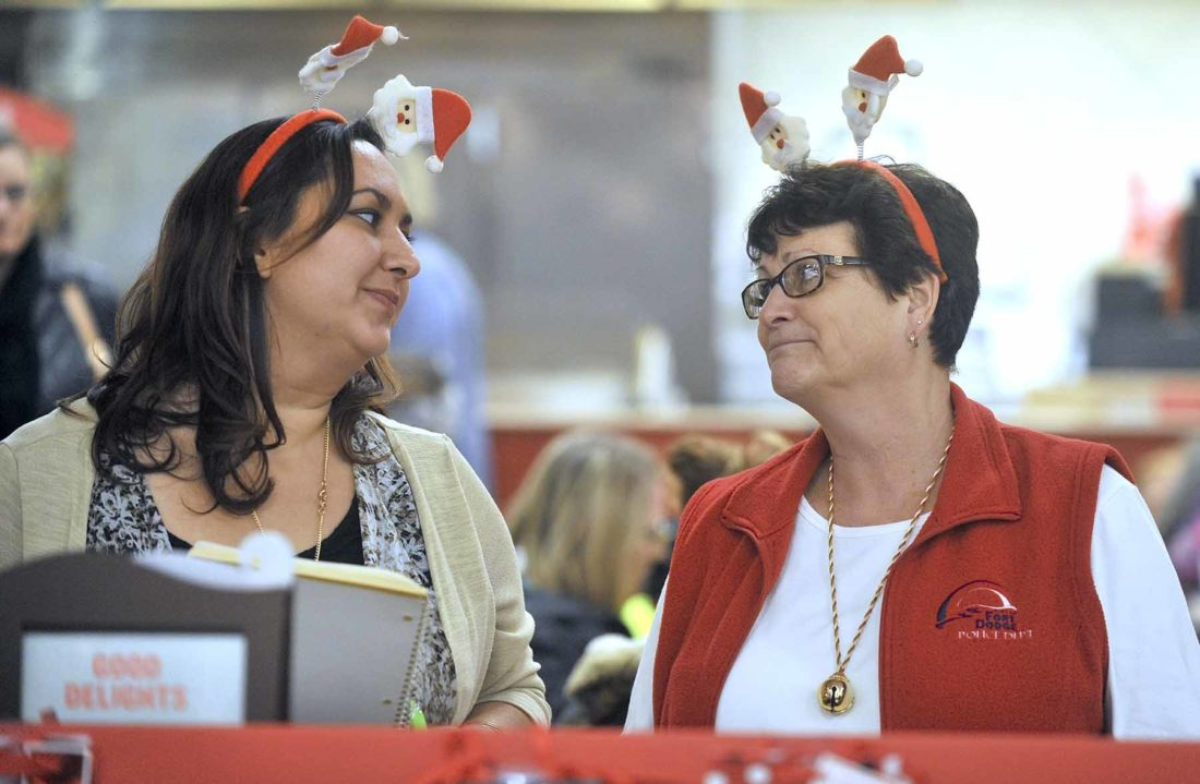 -Messenger photo by Hans Madsen  Retiring Fort Dodge Police secretary Sandy Markey, at right, works with new secretary Amber Maxson, at left, during the annual Santa Cops shopping night at Target.
