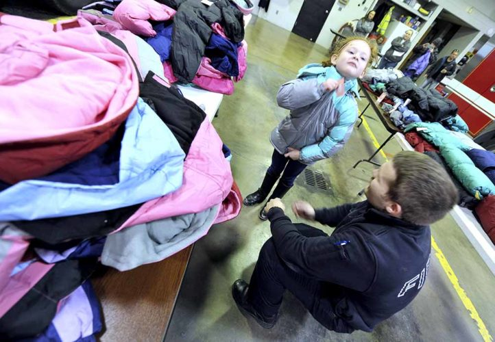 -Messenger photo by Hans Madsen  Fort Dodge firefighter Spencer Gratton helps make sure that Daysire Palmarez's new coat fits her properly Tuesday afternoon during the annual Operation Warm coat distribution at the fire station.