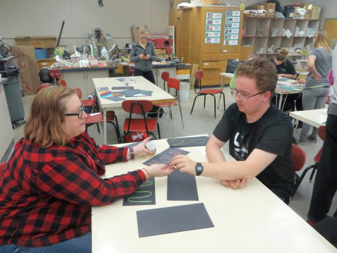 -Submitted photo   Amanda Peterlin, Circle of Friends Art instructor, helps Nolan Slininger, mentee, choose chalk to use on his project.