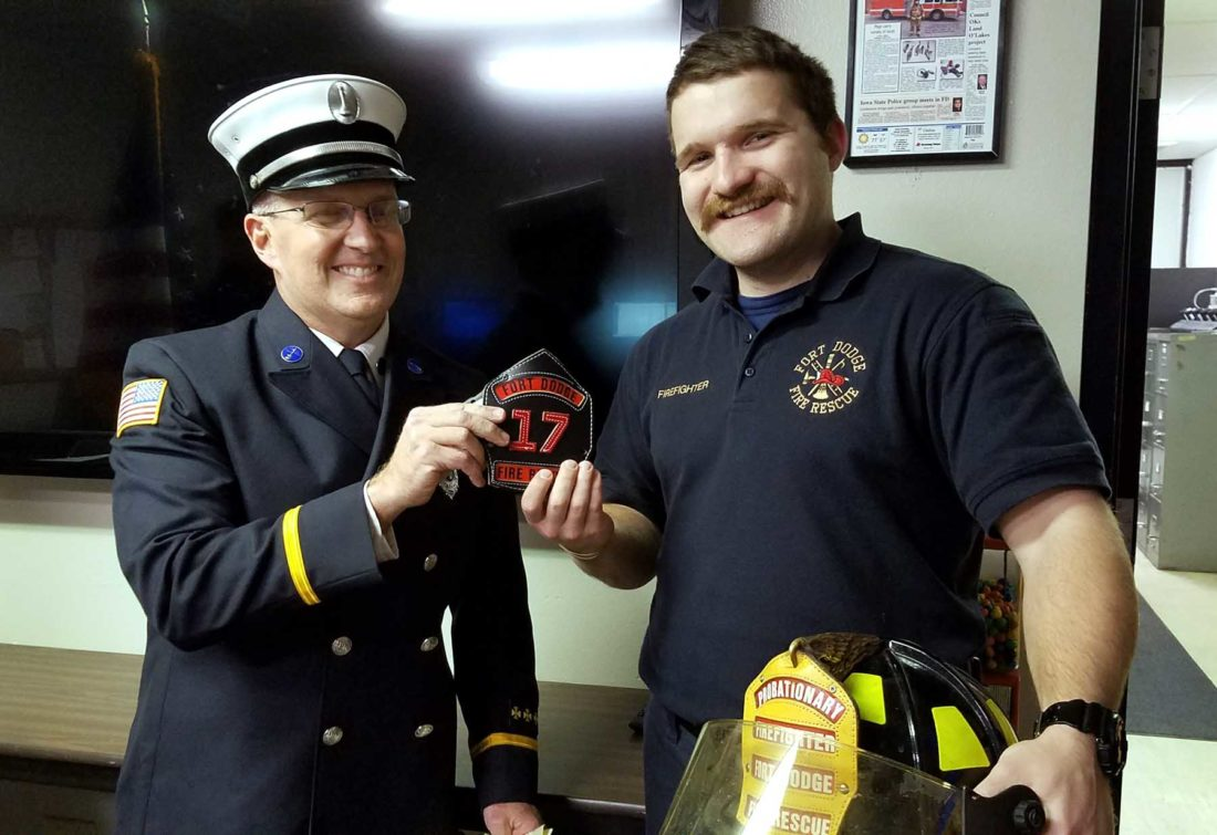-Submitted photo   Former probationary firefighter Spencer Gratton got his helmet badge Saturday night after he successfully completed his probationary year with the Fort Dodge Fire Department. Lt. Mitch Halverson, at left, along with Lt. Tom Ubben, presented it to him during a short graduation ceremony at the station. Gratton is a Critical Care Paramedic, and previously worked in the Quad Cities for AMT Ambulance. He was also a volunteer firefighter at Bettendorf Fire Rescue and he works part-time for Van Diest Medical Center in Webster City.