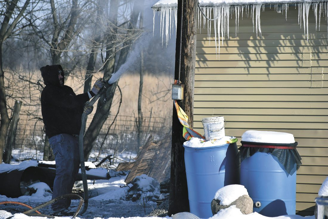 -Messenger photo by Chad Thompson  Brandon Osborne, a Dayton volunteer firefighter, shoots water at the side of a garage near Lehigh Tuesday afternoon. According to Aaron Morris, Lehigh volunteer fire chief, the north wall of the structure caught fire from a nearby wood stove. Morris said the garage, located at 1096 290th St., was empty at the time of the fire. No one was injured, he said. Lehigh Volunteer Fire Department, Dayton Volunteer Fire Department and the Iowa Department of Natural Resources were on scene.