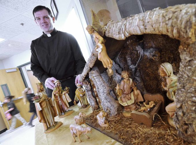 -Messenger photo by Hans Madsen  Rev. Patrick Behm, a priest with Holy Trinity Parish, poses next to a Nativity scene at St. Edmond Catholic School.