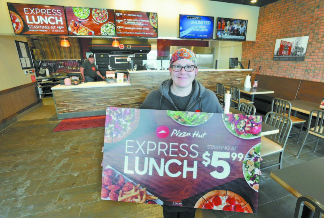 -Messenger photo by Hans Madsen  Fort Dodge Pizza Hut manager Jeaannie McKinney holds a sign for their new Express Lunch in the dining area of their new location at 2516 Fifth Ave. S.