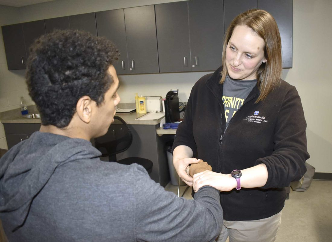 -Messenger photo by Chad Thompson  Bre Drees, an athletic trainer for UnityPoint Health, assesses the wrist of Brayden Bell, 17, a senior at Fort Dodge Senior High, recently.