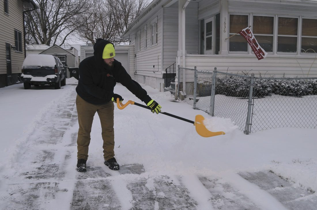-Messenger photo by Peter Kaspari  Trenton Larsen, of Fort Dodge, throws some snow off of a shovel on Eighth Avenue North Thursday.