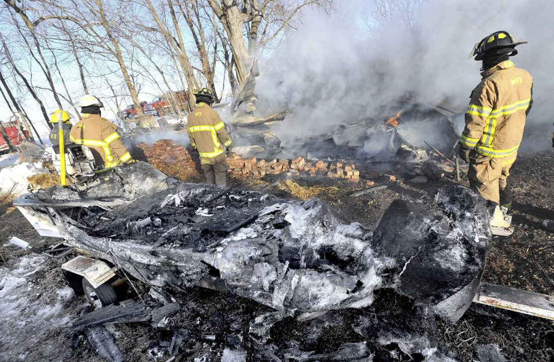 -Messenger photo by Hans Madsen  Framed by a fishing boat destroyed in the blaze, firefighters work on putting out the remains of a garage that burned Friday afternoon at 1227 210th Street near Barnum.