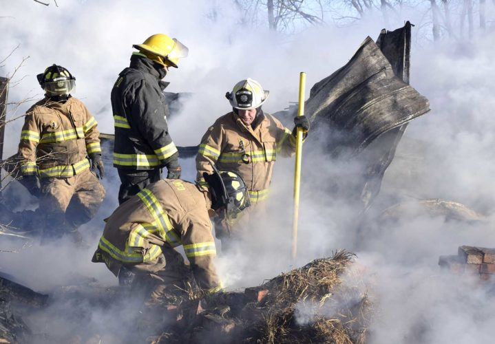 -Messenger photo by Peter Kaspari  Moorland firefighters clear out hay and other debris while battling a garage fire in Barnum Friday afternoon.