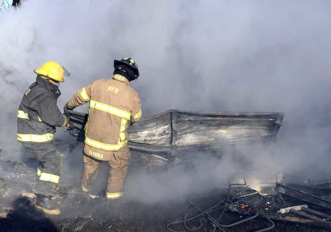 -Messenger photo by Peter Kaspari  Moorland firefighters drag the overhead door that was once attached to a garage away from a smoldering pile Friday afternoon in Barnum.