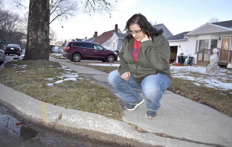 -Messenger photo by Chad Thompson  Gina Grobe, of Fort Dodge, is shown near Oleson Park Avenue outside of her home recently. A motorist was killed earlier this year when he hopped this curb and crashed into Grobes parked car in the driveway.
