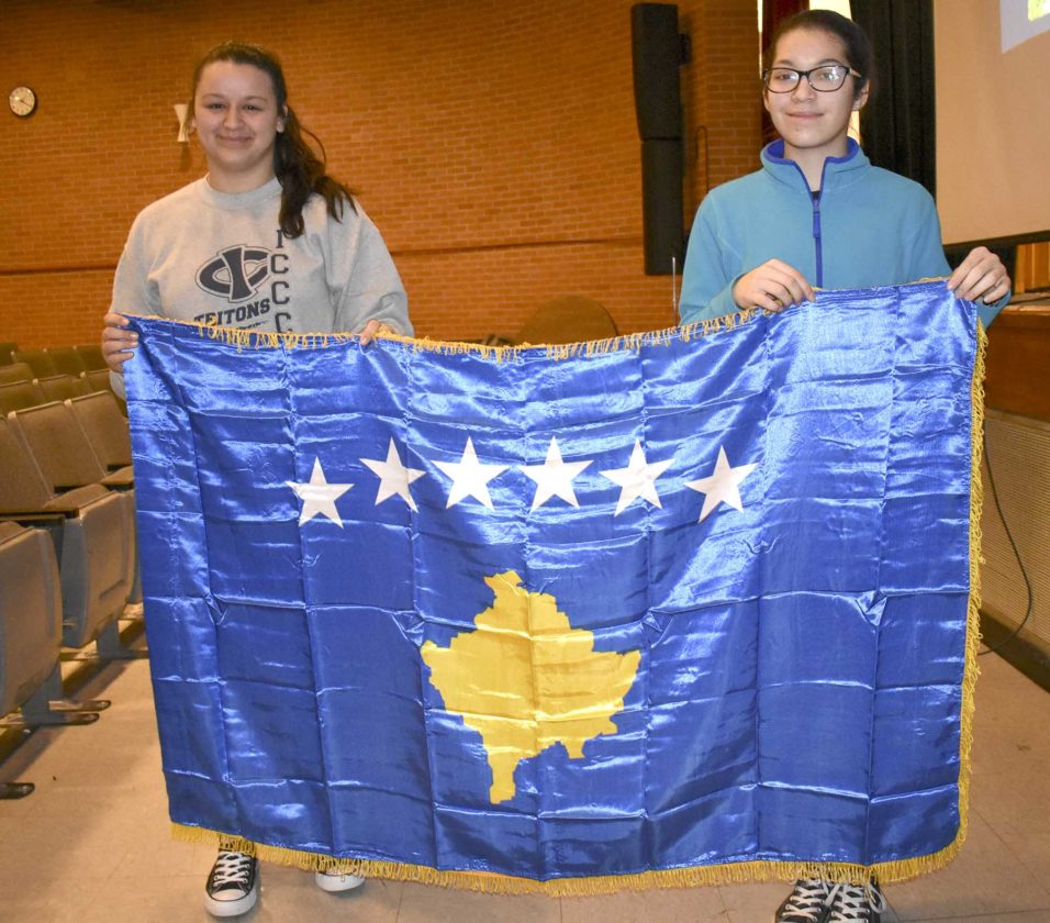 -Messenger photo by Chad Thompson  MaKayla Pingel, 18, a senior at Fort Dodge Senior High, left, and Jeannie Boro, 16, a junior at FDSH, hold up Kosovo's flag at the school recently.
