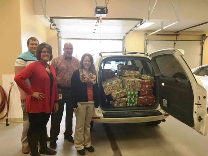 Decker Truck Line Inc. made Christmas merrier for a family identified through the Upper Des Moines Opportunity office. Pictured from left are Brad Baade, Teresa Otto, Tim Burns and Sammi Johnson with presents for the family.