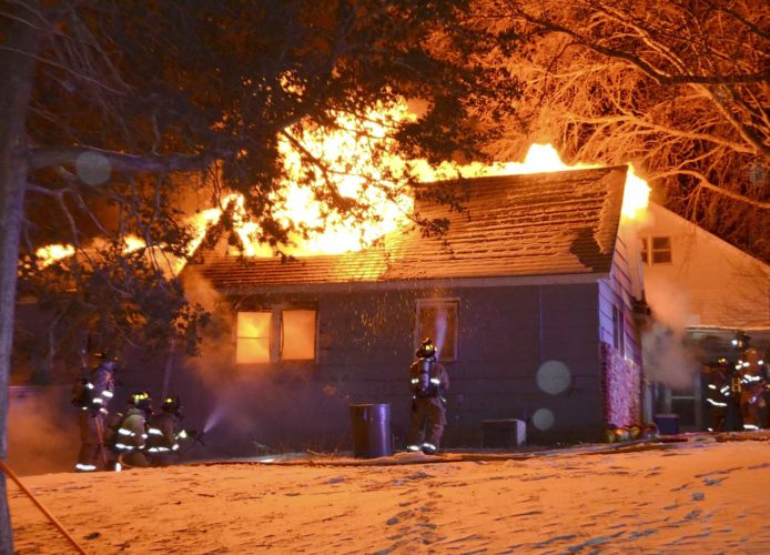 Messenger photo by Bill Shea  Flames and smoke billow from the roof of the house at 1505 L St. Monday night as firefighters work to put out the blaze. The fire claimed the life of a dog that was inside.