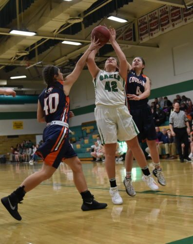 -Messenger photo by Britt Kudla Livi Huss of St. Edmond shoots around Manson NW Webster Samantha Ruhland (4) and Bailey Kenyon on Monday